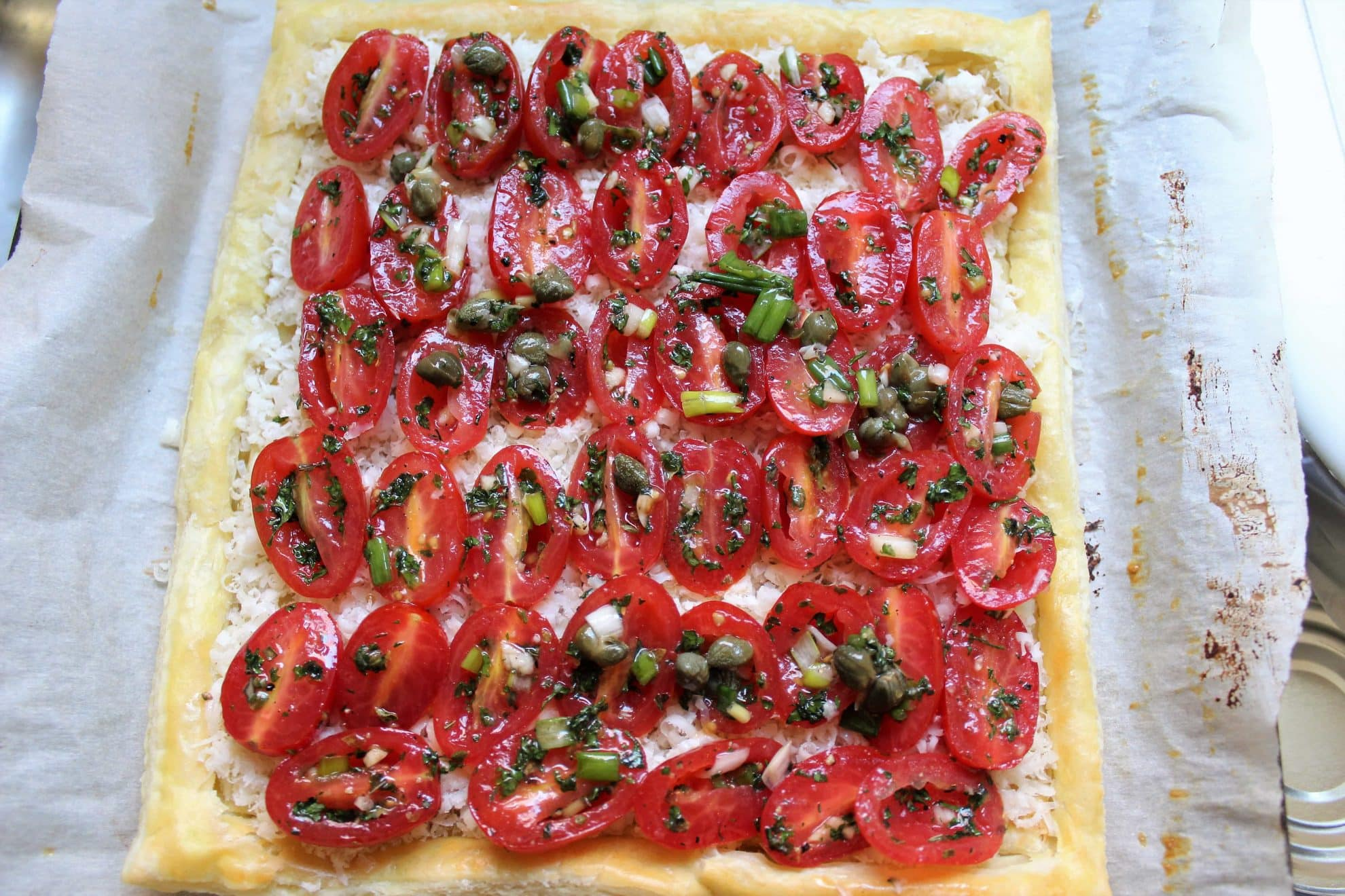 herb tomatoes laid over puff pastry in pan