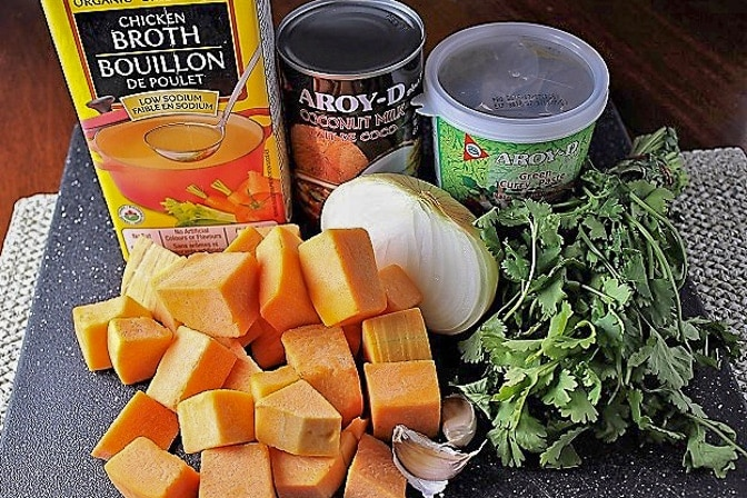 butternut squash, coconut milk, curry paste, chicken broth, parsley, onion, garlic, potato on cutting board