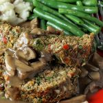 meatloaf with mushroom gravy on red plate with mashed potatoes and green beans