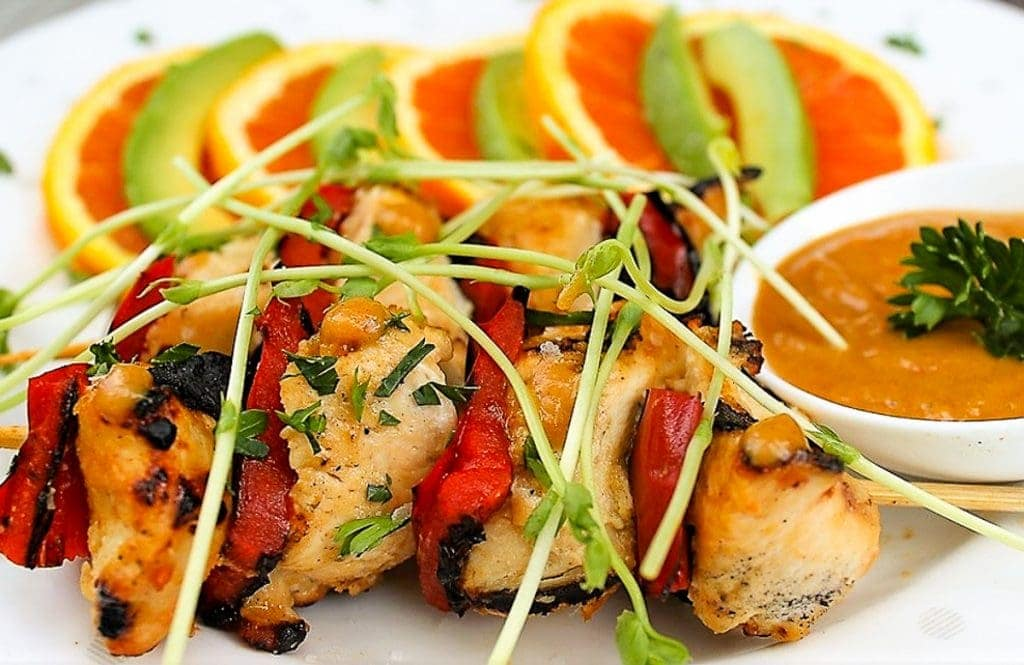 Peanut chicken on skewer on plate with dish of peanut sauce and slices of orange and avocado. topped with pea sprouts