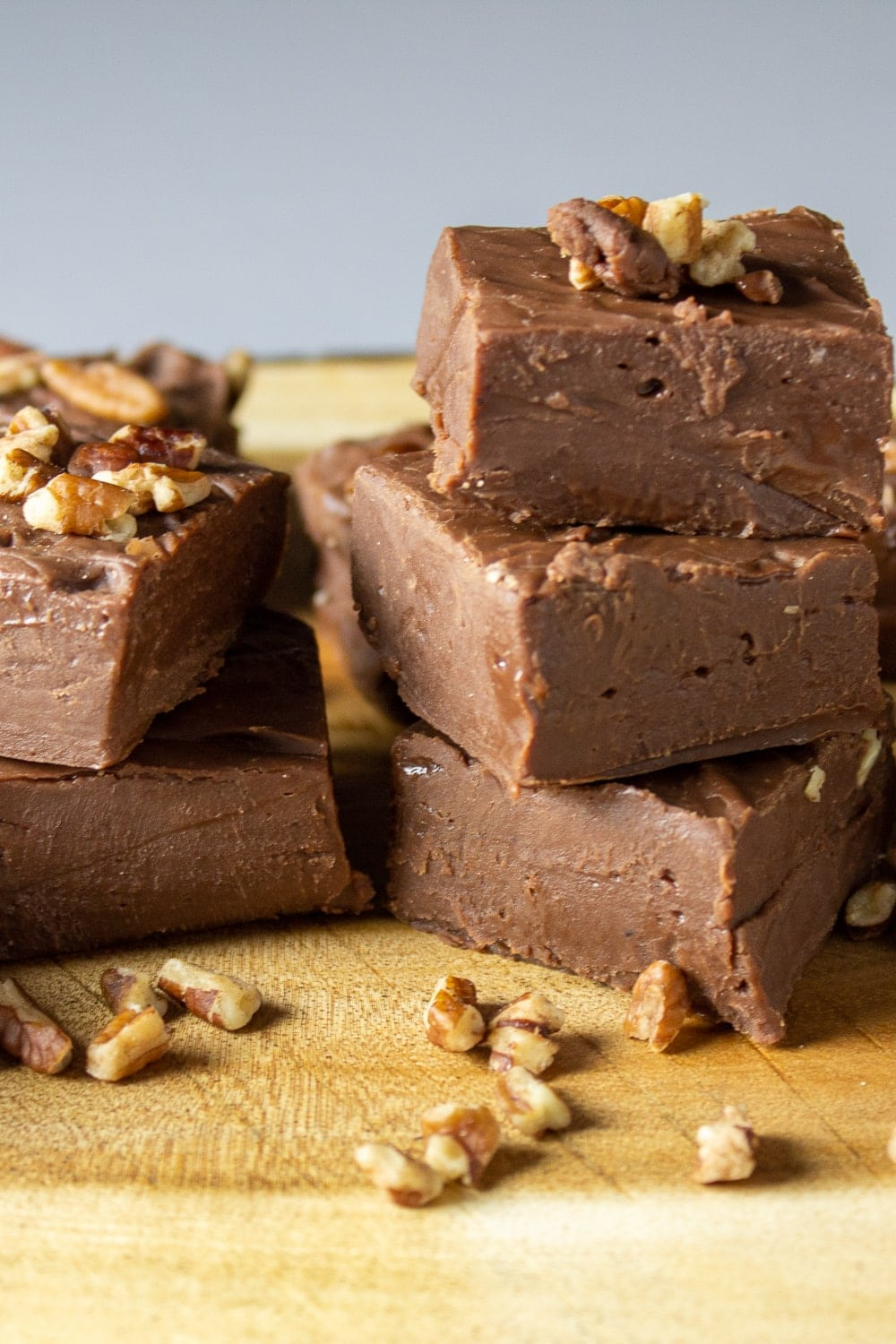 pieces of easy chocolate fudge on serving board with nuts on top p2