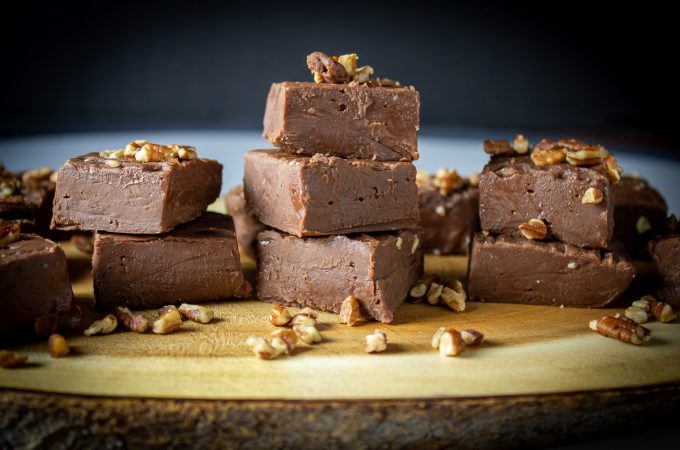 chocolate fudge pieces with nuts stacked on serving board f