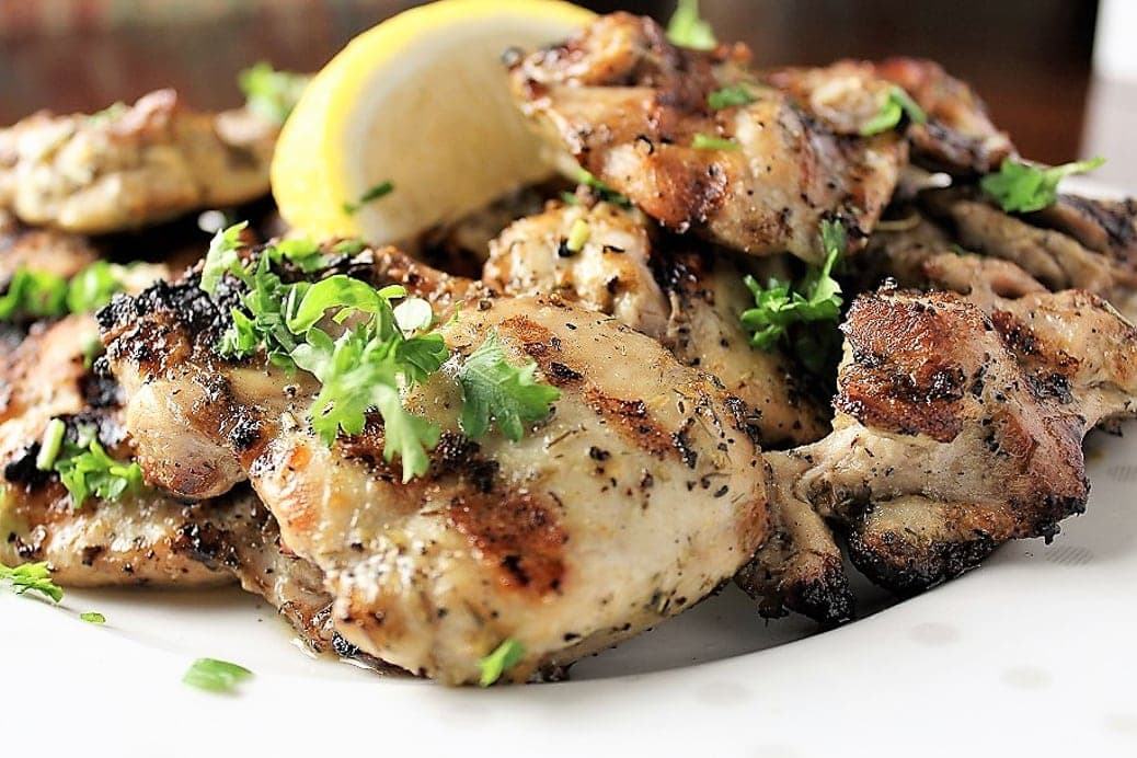 pieces of Mediterranean marinated grilled chicken on a plate with lemon wedge