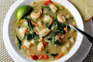 Shrimp Chowder Thai Style in a bowl with buttered bread on the side