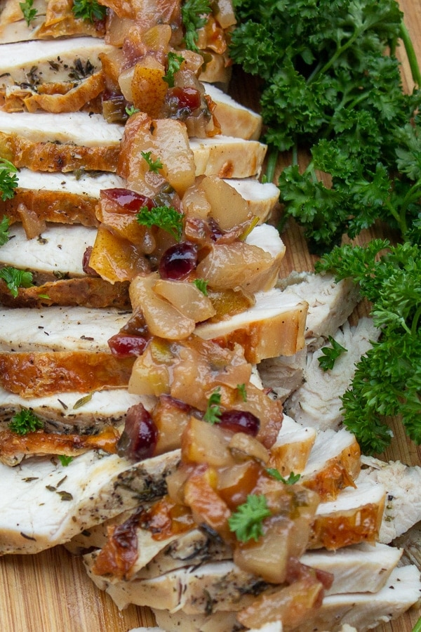 sliced turkey breast on cutting board with pear chutney spooned on top p1