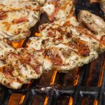 Mediterranean marinated grilled chicken on the grill with hot flames underneath p