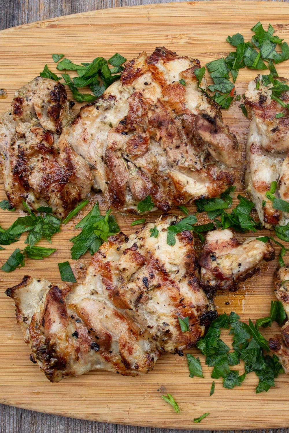 Mediterranean marinated grilled chicken on cutting board with parsley p