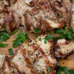 Mediterranean marinated grilled chicken on cutting board with parsley p1
