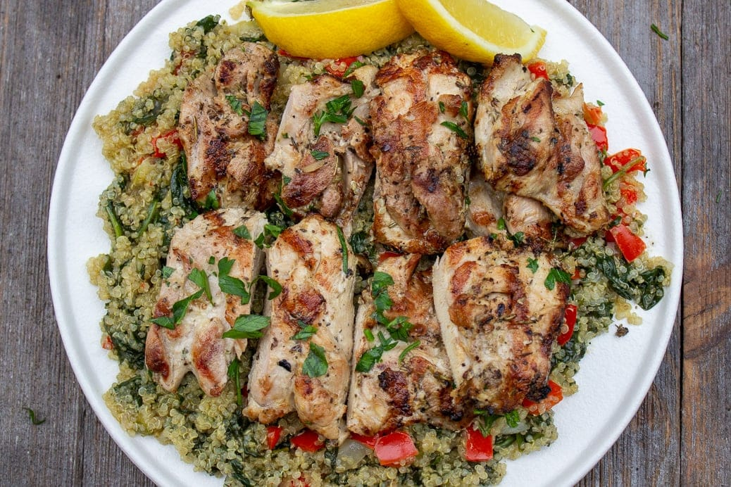 Mediterranean marinated grilled chicken cut into pieces laid over quinoa on a plate with lemon wedges