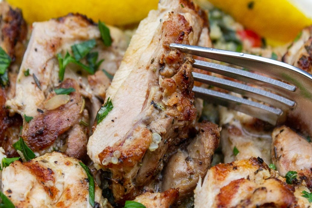 Mediterranean marinated grilled chicken piece on a fork (close up) over chicken on plate with lemon