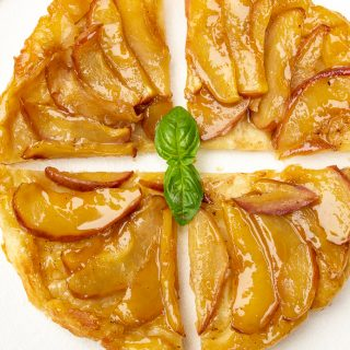 puff pastry apple tart cut into 4 slices on plate