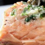 piece of salmon on plate showing inside with caper sauce on top p3