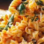 tomato spinach pasta on plate with bread p