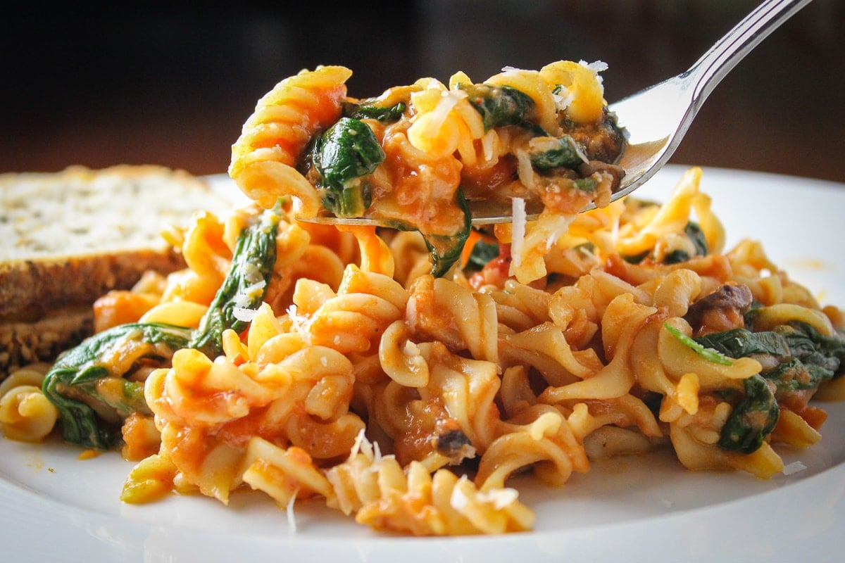 Cheesy Tomato Spinach Pasta on plate with bread fff