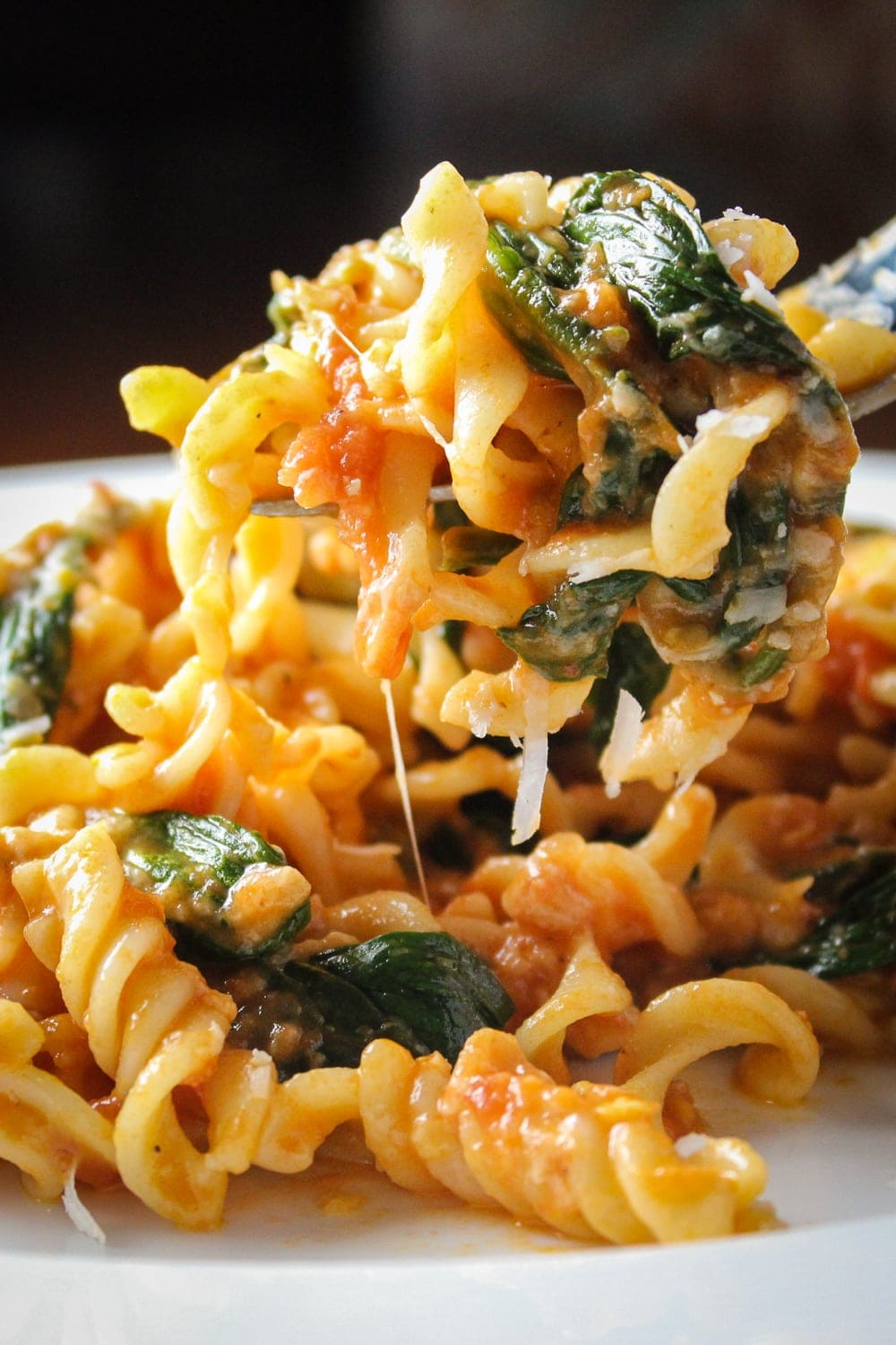 tomato spinach pasta on plate with bread p1