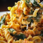 tomato spinach pasta lifted on fork over bowl
