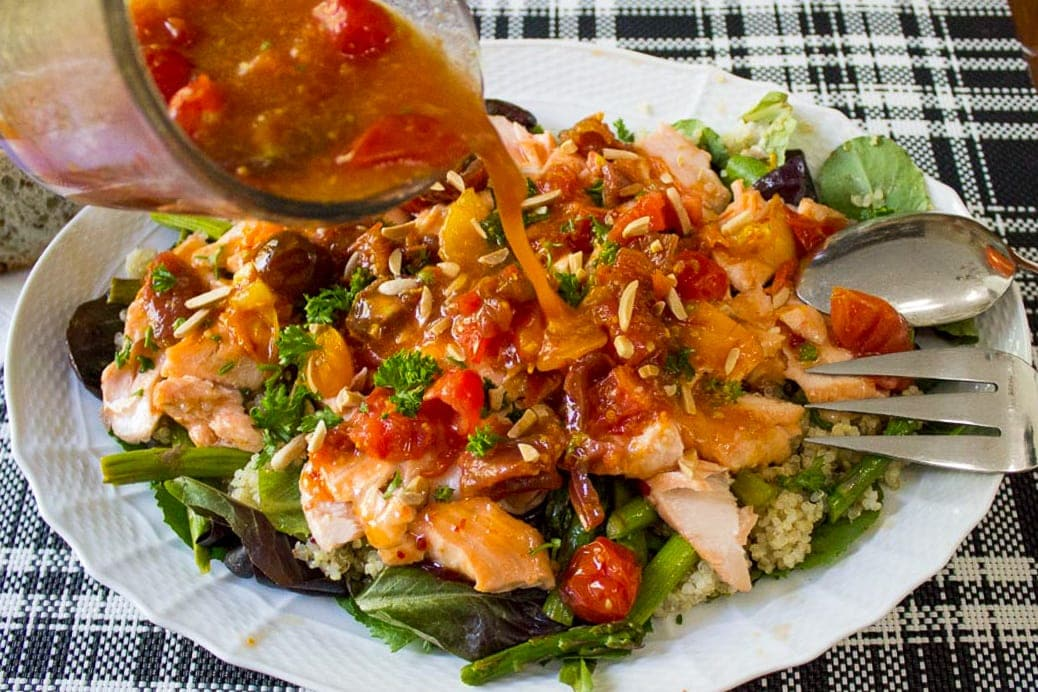 Warm Salmon Salad with Tomato Citrus Sauce being poured on it