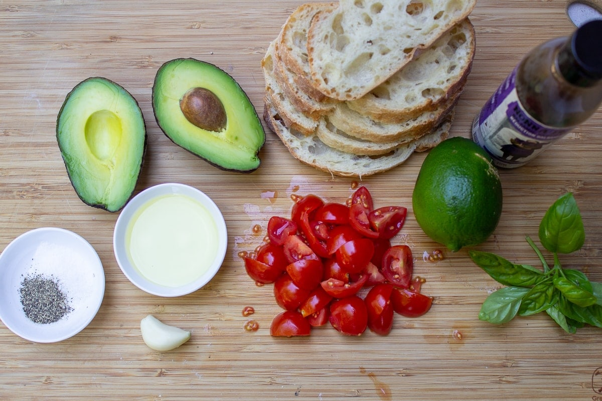bread slices, avocado, oil, tomatoes, lime, garlic salt and pepper
