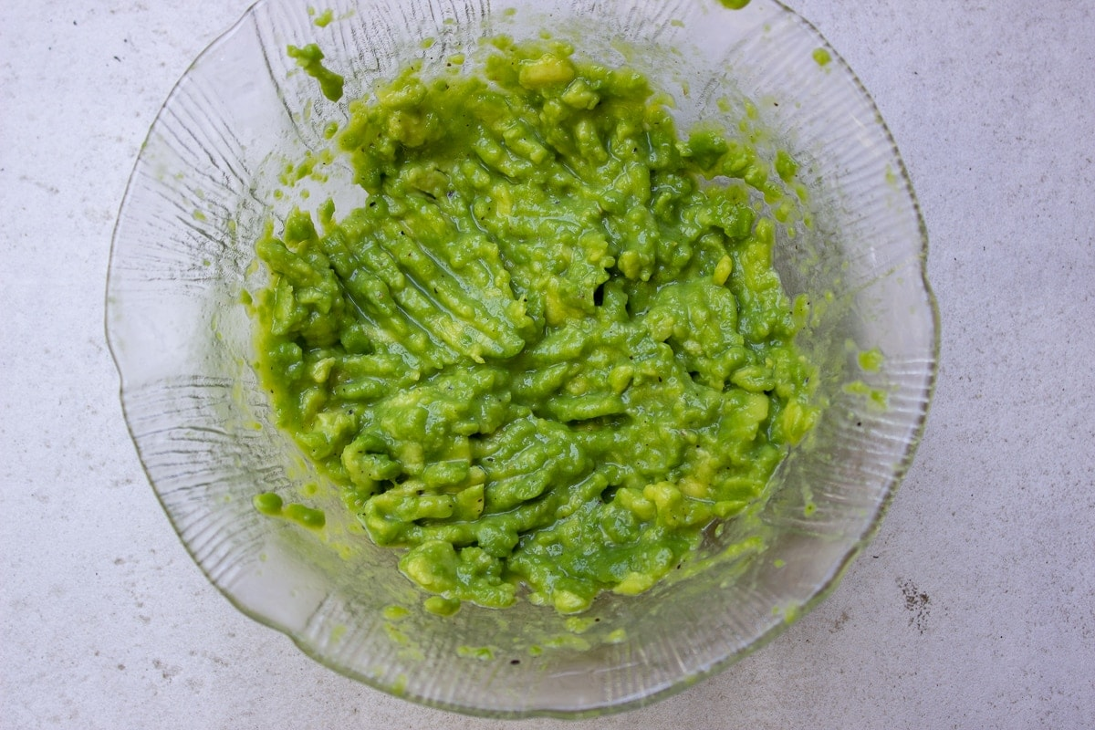 mashed avocado with lime salt pepper in bowl