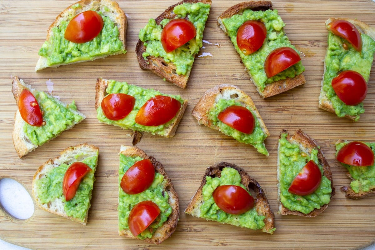 cut up toast spread with avocado and tomatoes on cutting board