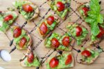 Avocado Crostini with Balsamic Drizzle on cutting board
