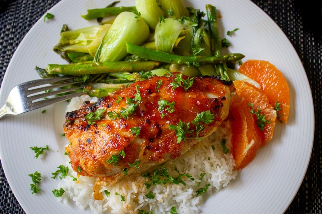 apricot chicken breast on plate with rice and bok choy and orange slices