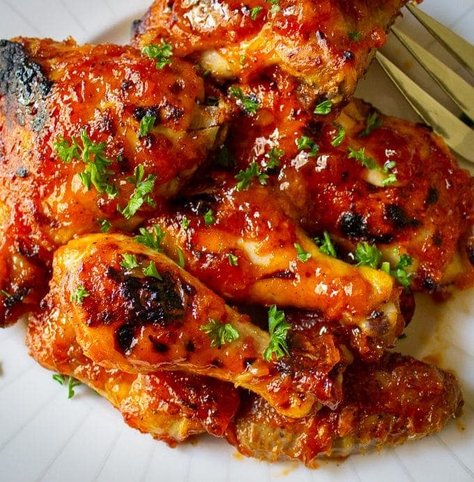 Baked Apricot Chicken pieces piled on plate on black placemat