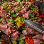 Sous Vide Steak with Balsamic Sauce sliced in a salad with veggies and sesame seeds p on a plate p