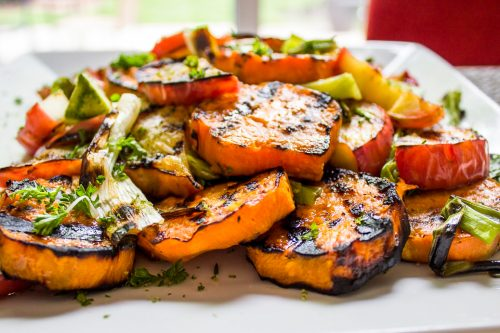 Grilled Honey-Lime Sweet Potatoes, apples and green onins on a plate f