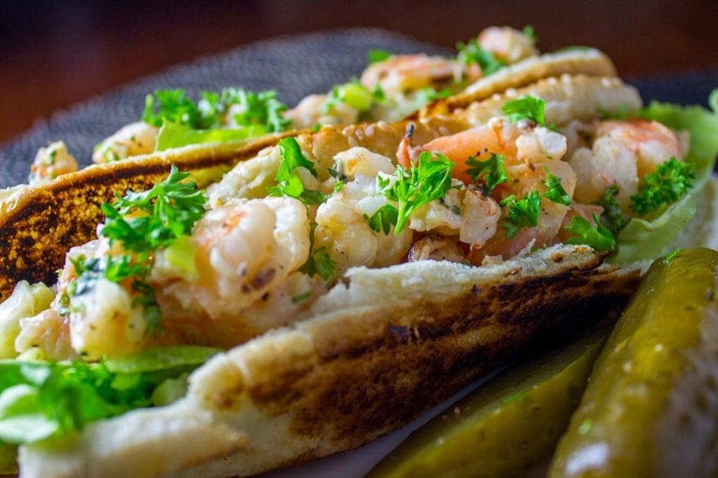 grilled shrimp rolls on a plate with a pickle