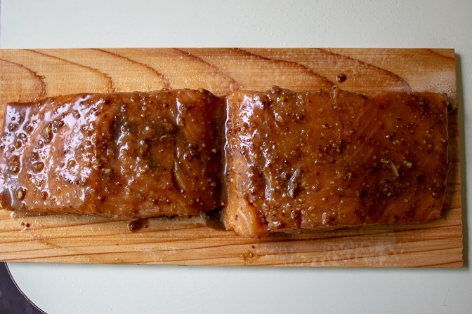 maple glaze brushed on salmon fillets on plank