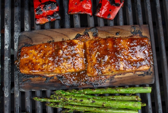 salmon on planks grilling along with peppers and asparagus