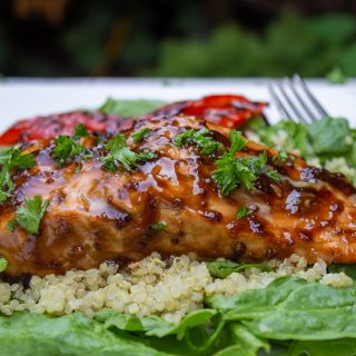 Maple balsamic planked salmon over spinach and quinoa on plate