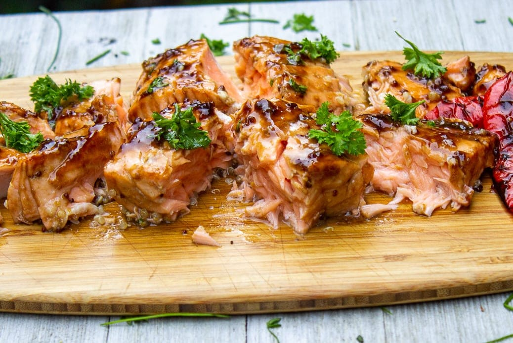 Maple balsamic planked salmon cut in pieces on cutting board