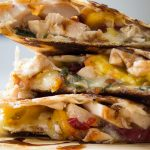 chicken quesadilla with brie and peaches stacked on cutting board