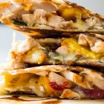 chicken quesadilla wedges stacked on cutting board p