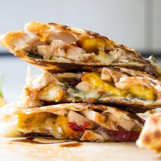 stack of Chicken Quesadilla wedges on cutting board fff