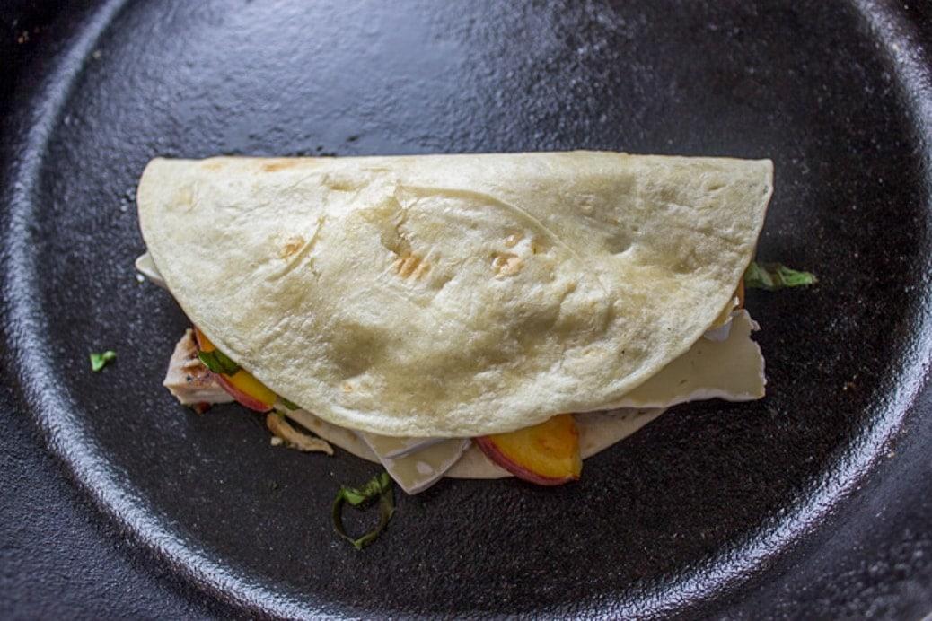 half tortilla folded over filled tortilla half in pan