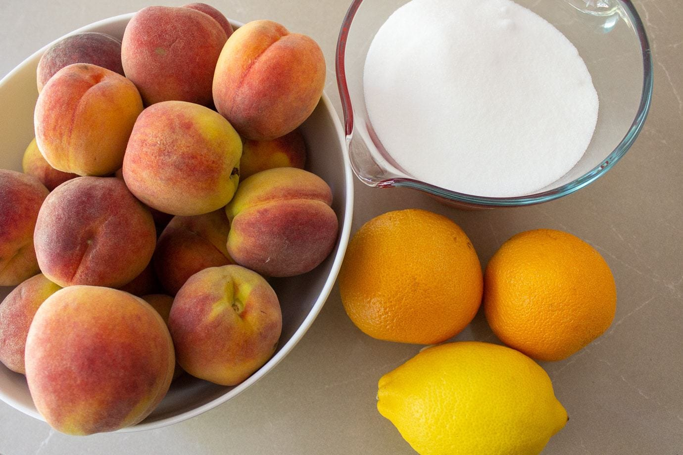 peaches in a bowl, oranges, sugar, lemon