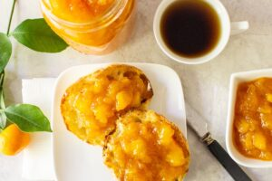 Peach Marmalade on english muffins on plate with cup of jam, coffee and jar of jam in background ff