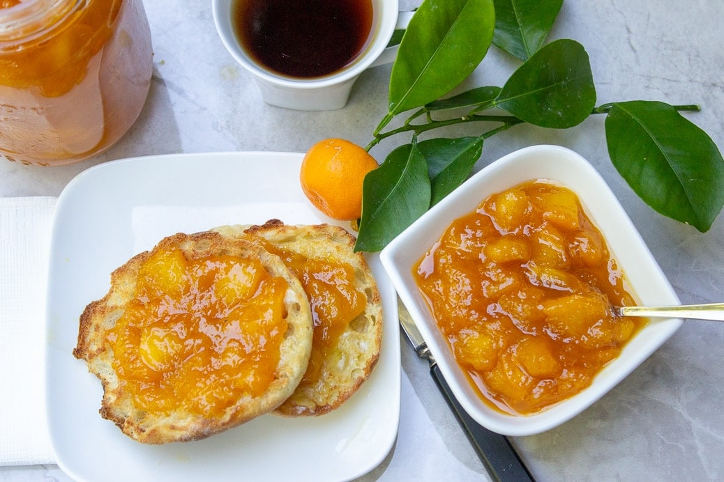 peach marmalade on english muffin on plate with jar of marmalade beside and coffee 3