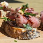 beef crostini with drizzle of balsamic reduction sitting on cutting board