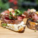 Beef Crostini with Horseradish Aioli served on a cutting board p1