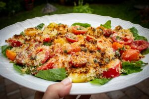 Broiled Cherry Tomatoes with Cheese and Panko Crumbs on a bed of spinach sitting on a plate