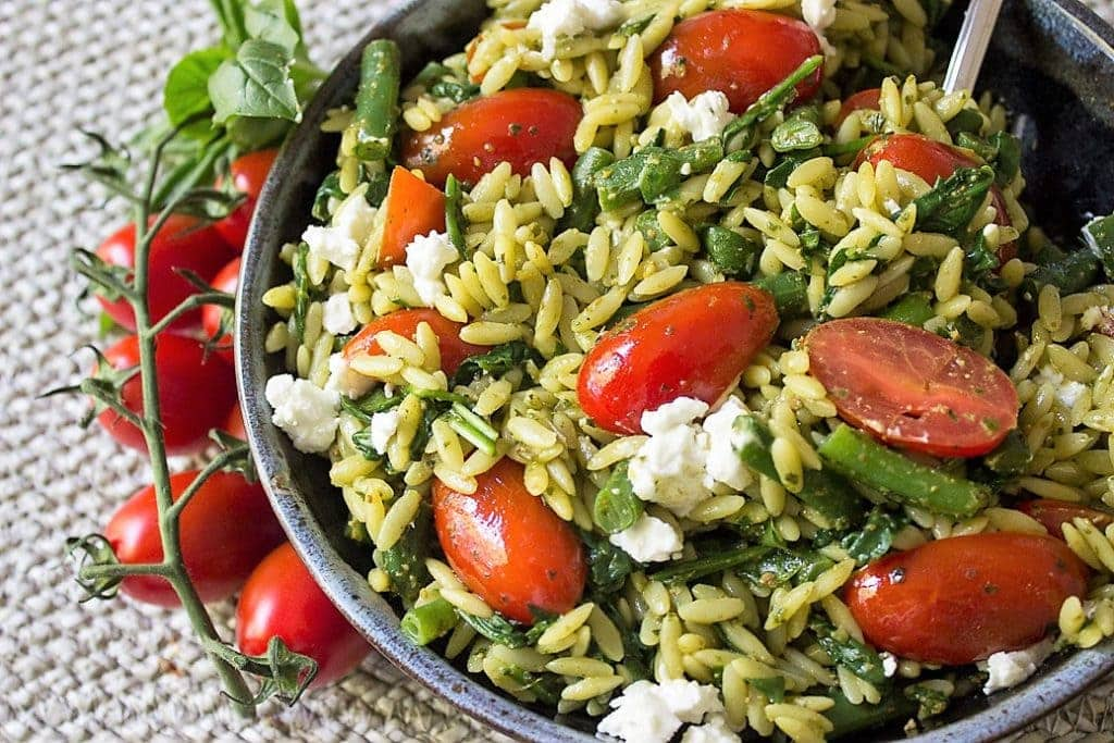 pesto and vegetable orzo in a bowl with vine tomatoes beside bowl