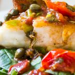 Roasted Halibut with Tomatoes and Capers on bed of spinach on a plate p1