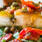 Roasted Halibut with Tomatoes and Capers on bed of spinach on a plate p