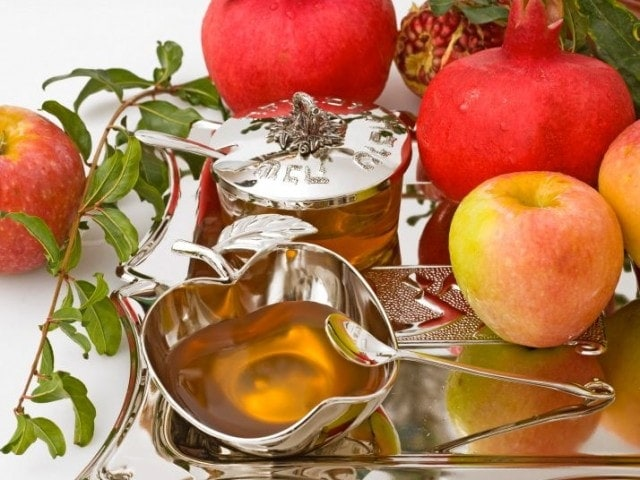apples and honey on table for Rosh Hashanah