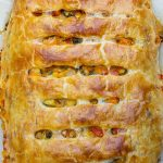 uncut vegetable strudel with goat cheese piece on parchment lined cutting board p