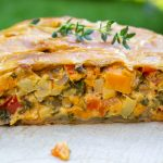 Vegetable Strudel in puff pastry cut open on parchment paper